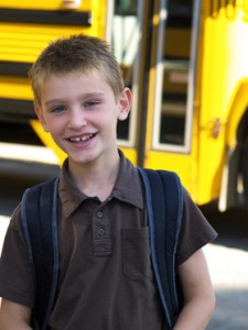 photo of boy by school bus